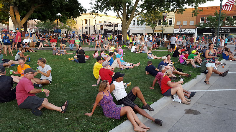 Townspeople and cyclists lounging in front of the band in Centerville